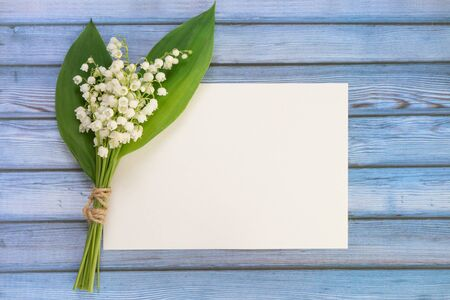 Bouquet of flowers lily of the valley and empty paper sheet on blue rustic table from above, white empty card, top view, space for text, flat lay.