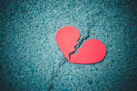 Red broken heart on asphalt background - dark and moody