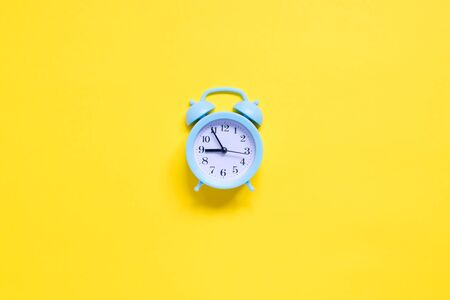 Blue alarm clock on yellow background
