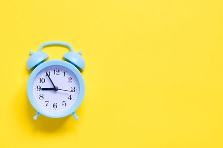 Blue alarm clock on yellow background. Flat lay. Free space for your text. Top view