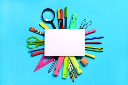Group of School or office supplies around a notepad on light blue background. Back to school concept. Space for text. Flat lay. Mock up 版權商用圖片