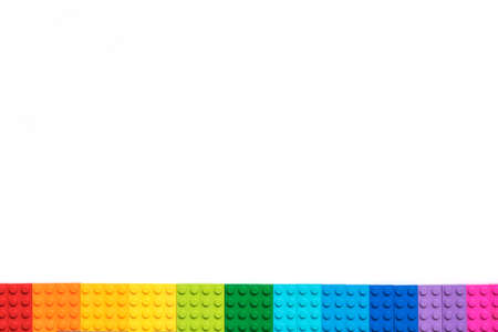 Border of Multicolor Plastick constructor bricks on white background. Popular toys.