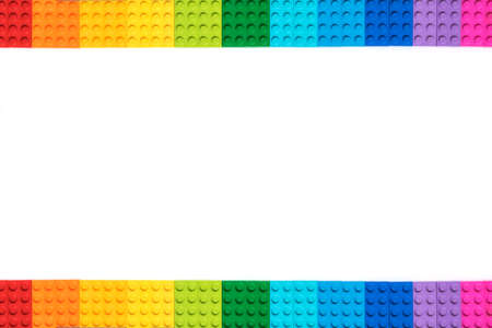 Frame of Multicolor constructor bricks on white background. Popular toys. 版權商用圖片