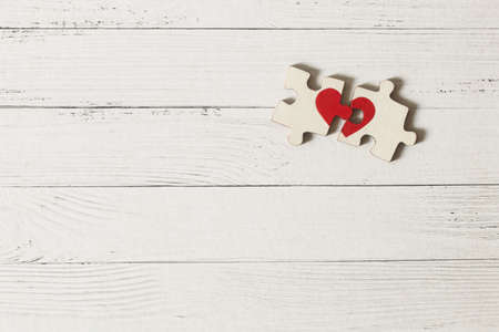 Red heart is drawn on the pieces of the wooden puzzle lying next to each other on white background. Love concept. St. Valentine day 版權商用圖片