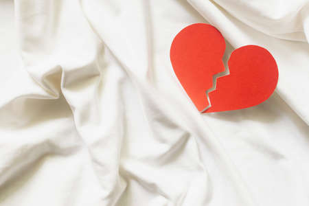 Broken red heart on white textile. divorce concept.