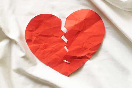 Broken red paper heart on white textile. divorce concept. 版權商用圖片
