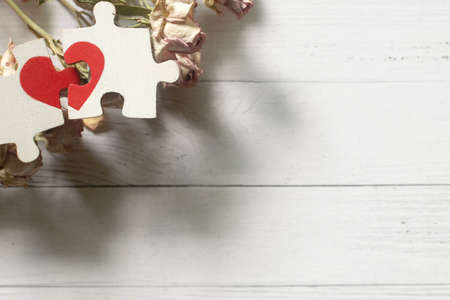 Red heart is drawn on the pieces of the wooden puzzle lying next to each other on white background. Love concept.