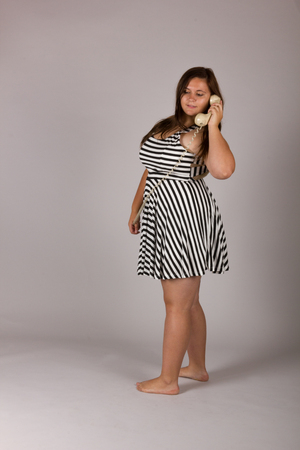 Beautiful Curvy Teenage Girl in Black and White Dress with Retro Telephone