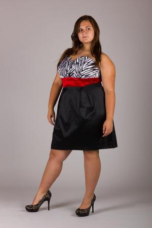 Bella ragazza formosa in abito a righe bianco e nero con scarpe nere Archivio Fotografico - 95328799