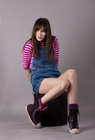 Cute Young Millennial Woman in Overalls Shoes Stripes on Velvet Stool Looking Left Cute