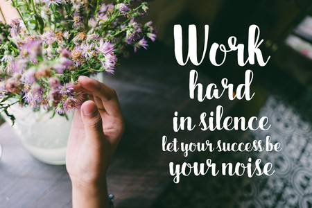 Life quote. Motivation quote on soft background. The hand touching purple flowers. Work hard in silence, let your success your noise. Stock fotó