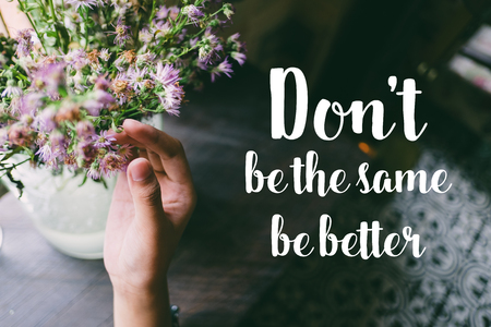 Life quote. Motivation quote on soft background. The hand touching purple flowers. Do not be the same be better. Stock Photo