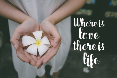 Love quote. Inspirational quote on the girl holding a white flower. Where is love, there is life.