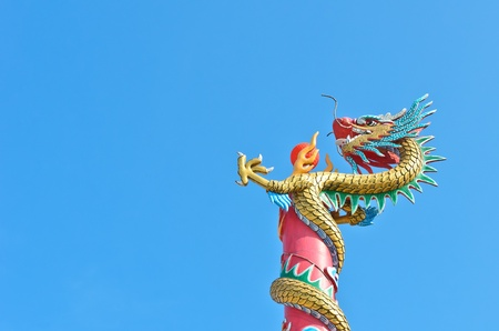 Drago Cinese avvolgere il palo con palla rossa nel cielo azzurro