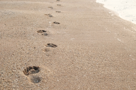 steps of footprint continue on sand beach