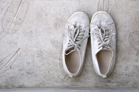 old white sneaker on cement floor