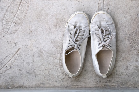 old white sneaker on cement floor
