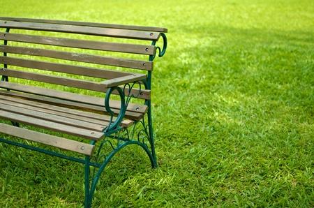 vista parzialmente fianco del sedile in legno con panca struttura metallica su erba