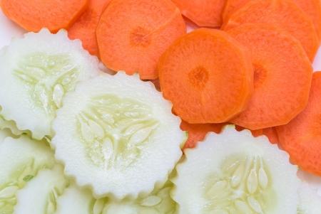 carote e cetrioli a fette in forma rotonda sul piatto bianco