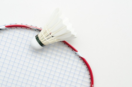 badminton racket in red color and light blue string with shuttlecock in top left partial view on white background Stock Photo