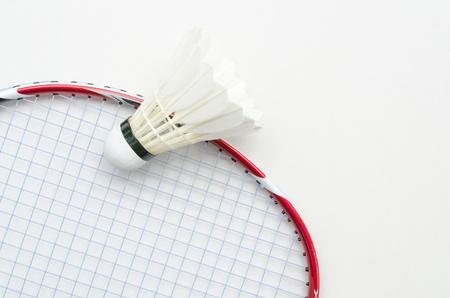 racchetta da badminton in colore rosso e blu con la luce stringa volano in alto a sinistra, vista parziale su sfondo bianco