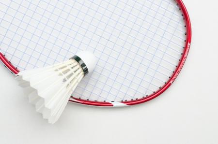 racchetta da badminton in colore rosso e la luce della stringa blu con volano in alto a destra parziale angolo vista su sfondo bianco Archivio Fotografico
