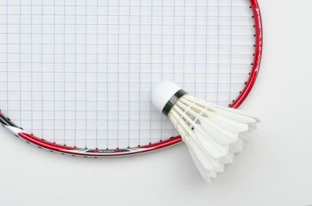 racchetta da badminton in colore rosso e blu con la luce stringa volano in alto a destra vista parziale su sfondo bianco