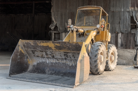 galvanize: old yellow tractor parks in factory with rustic galvanize metal in the background Stock Photo