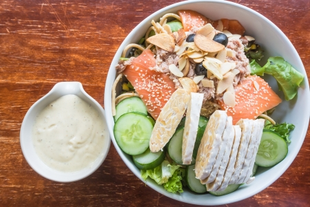salmon tuna salad with fresh green vegetable  and cream sauce in white ceramic bowl