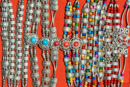 silver with colorful decorative stone bracelet of hill tribe in northern of thailand on red background photo