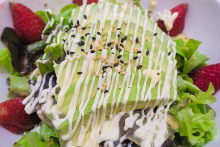 fresco mix di insalata di avocado con fragole verdura verde e sesamo bianco e nero sulla parte superiore