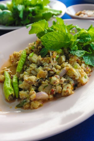 minced fish spicy salad with fresh green vegetable in background