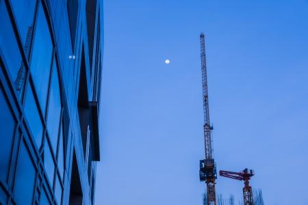 affari alto edificio con gru in metallo e la luna piena in cielo all'alba Archivio Fotografico