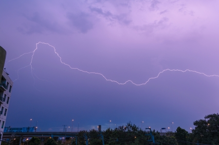 rain cloud lightning strike over city sky at twilight
