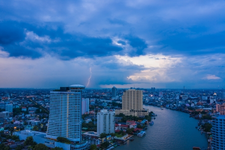 river in city with rain cloud lightning strike in background Stock Photo - 16654323