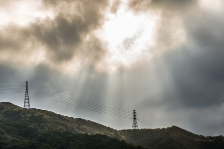 sun light beam through rain cloud over high voltage electrical wire and mountain Stock Photo - 16654319