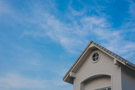 gable house: new grey house gable under blue cloud sky