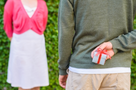 l'uomo nasconde argento con confezione regalo rosso del nastro sulla schiena di fronte a una donna in background Archivio Fotografico