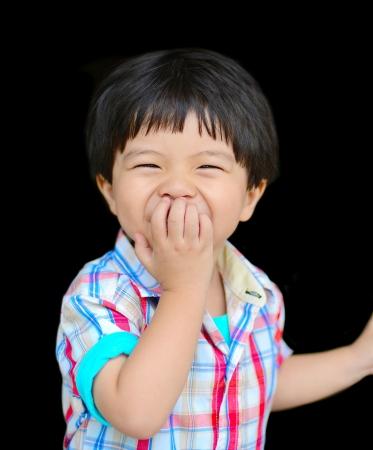 felice bambino che ride con una mano davanti alla bocca Archivio Fotografico