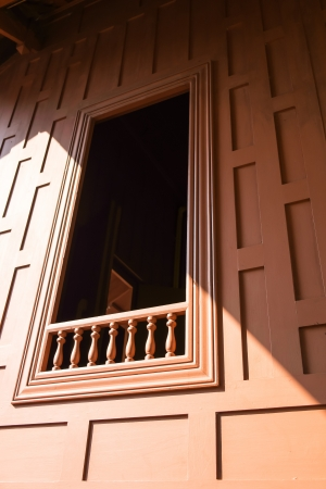 traditional window and wall of native thai house in low vertical angle view under afternoon sun