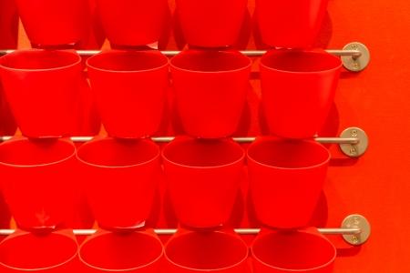 fila di tazza di plastica rossa appendere sulla visualizzazione della barra di metallo sulla parete Archivio Fotografico