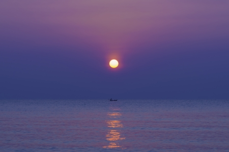 calm sea at dawn with full sun rise and twilight sky Stock Photo