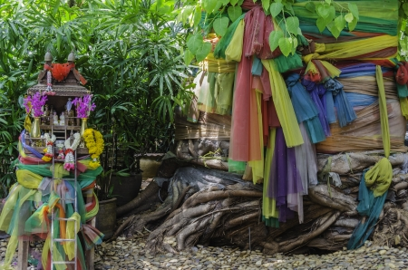 traditional thai spirit house and big tree with colorful fabric wrap around photo