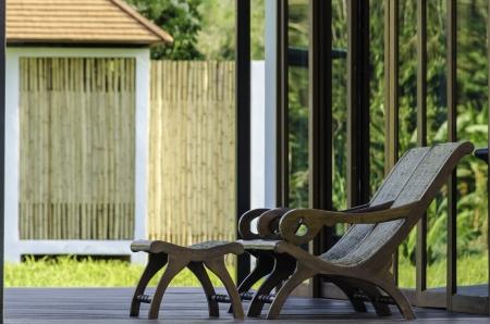 artigianato del legno poltrona sulla terrazza di legno in un ambiente verde con casa a sfondo esotico