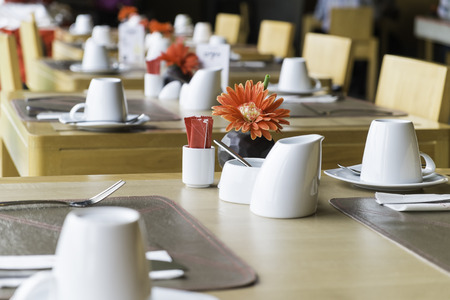 public wood dining table set with white porcelain tableware and decorative objects Stock Photo
