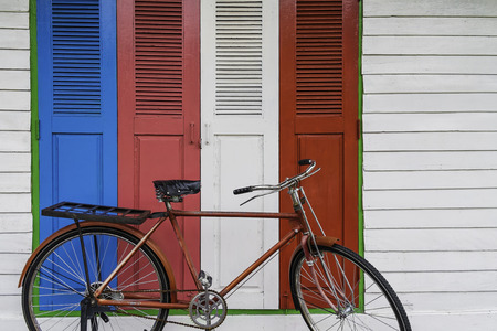 red vintage bicycle in colorful old wood door and white stripe wall   background Stock Photo