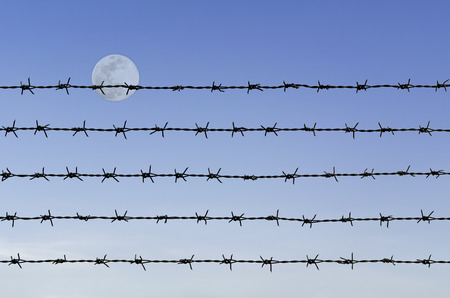 row of rustic barbed wire over abstract full moon sky background photo