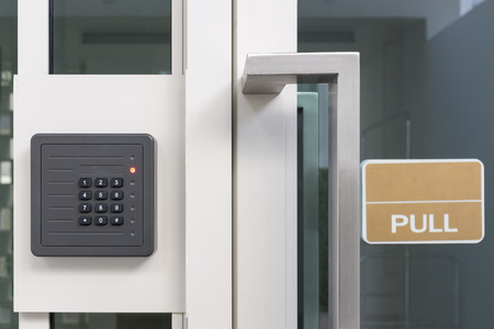 office entrance: electronic access control door box with numeric keypad next to white aluminium frame glass door with sign