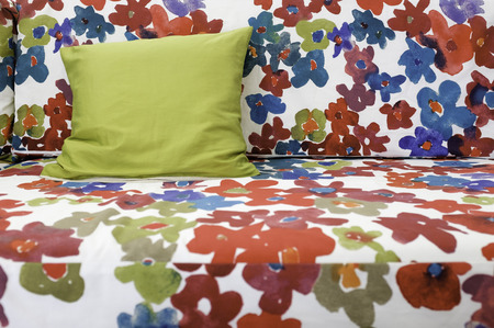 colorful graphic flower print fabric sofa with green silk pilow Stock Photo
