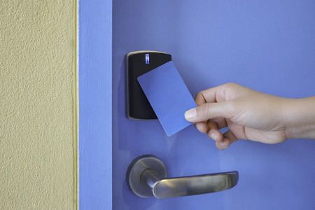 hand hold key card touch on black electronic key pad lock access control with stainless steel door handle on blue door